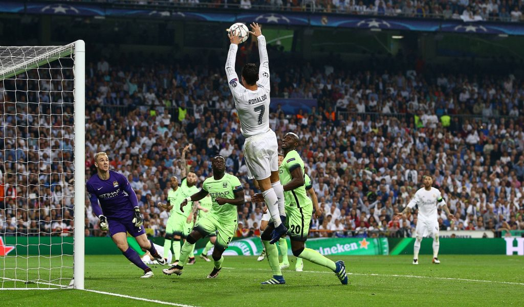 Cristiano Ronaldo of Real Madrid handballs the ball into the goal and is shown a yellow card during